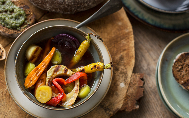 Vegetable soup with roasted and grilled vegetables served with walnut pesto