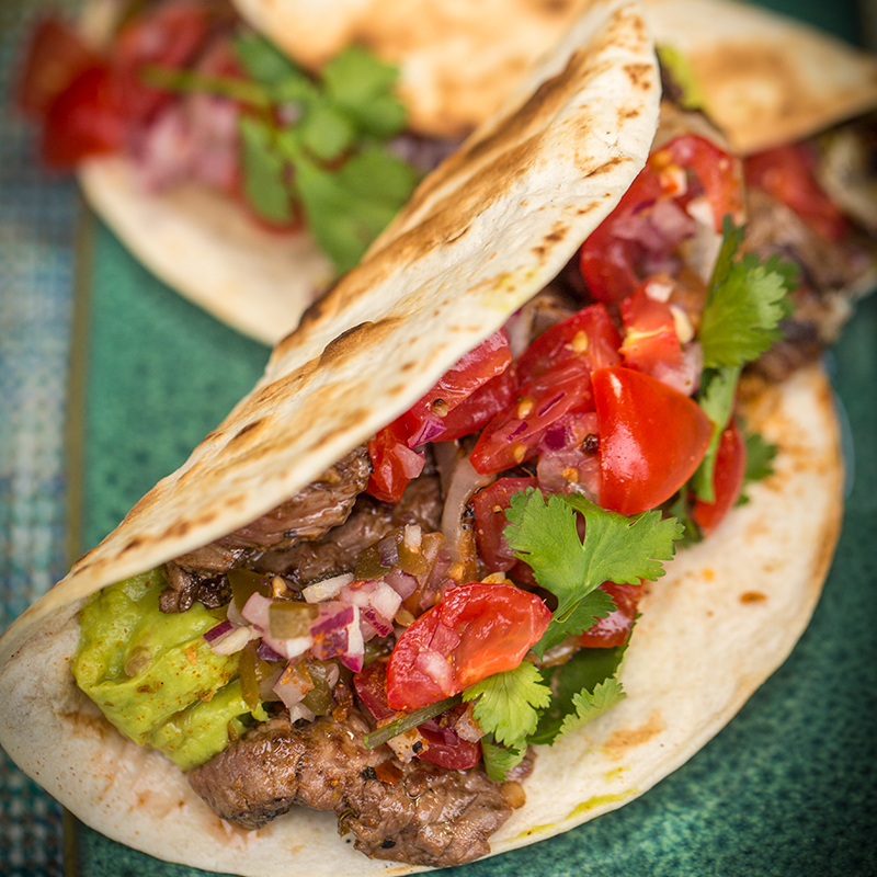 Tacos with flank steak, guacamole and pico de gallo
